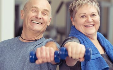 A picture of a couple working out in a friendly gym environment.